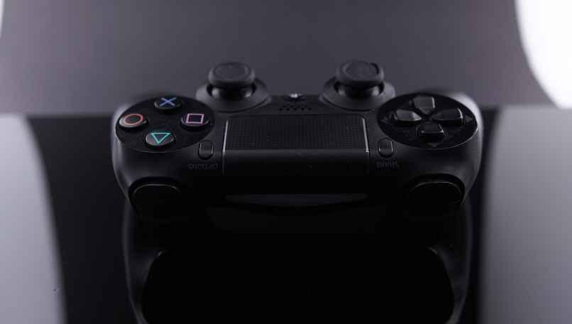 consola ps4 con su control para jugar
